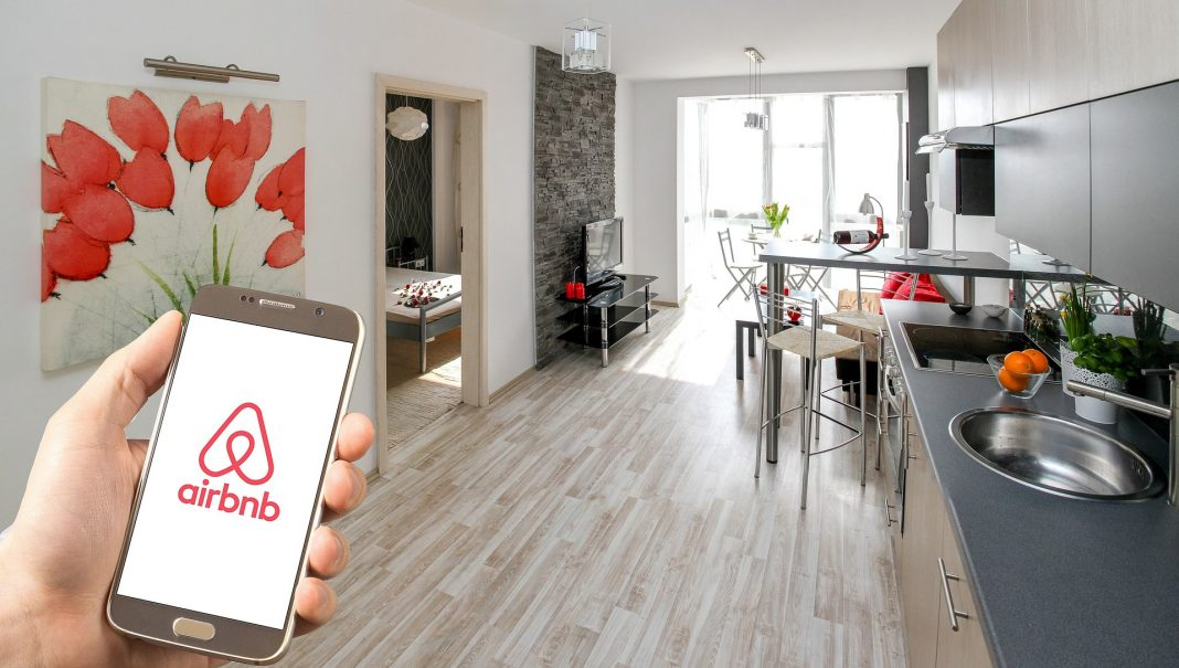 A mobile version of AirBnb on a mobile phone inside a clean apartment
