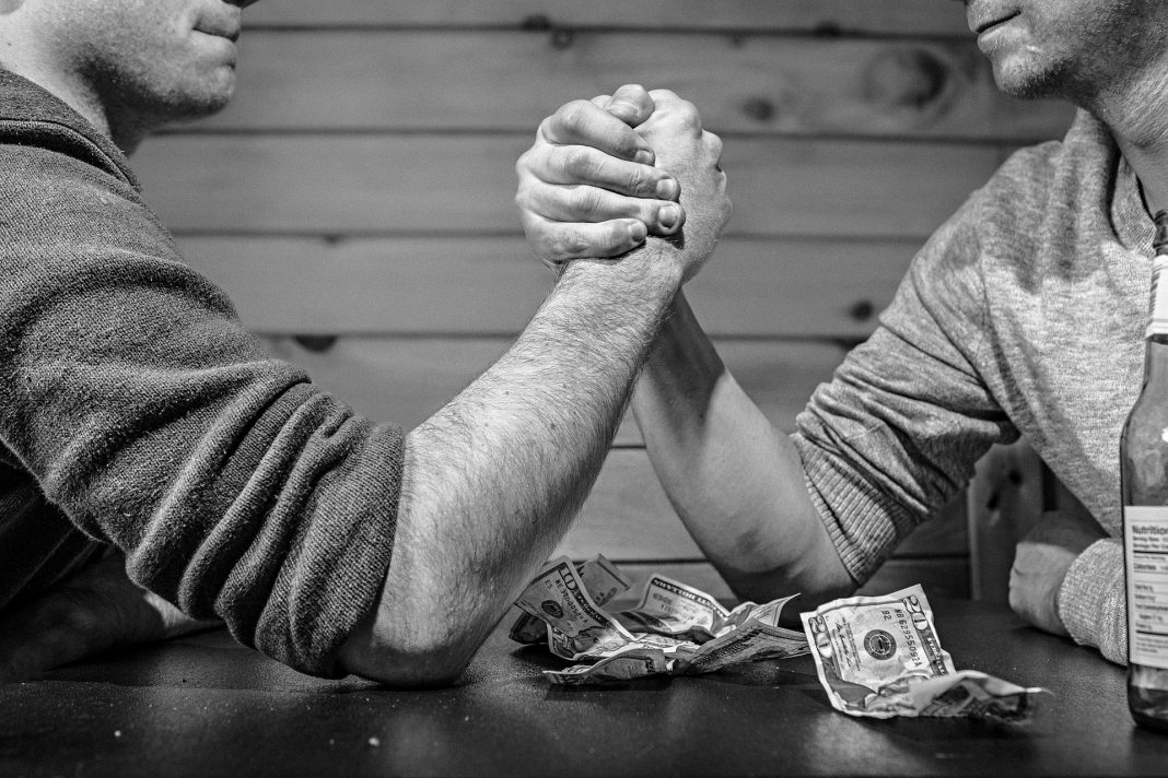 Two men arm wrestling with gambling money on the table