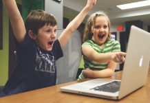 Two children looking excited while consuming content on a laptop
