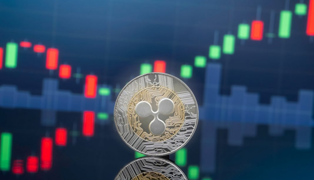 A silver coin with XRP-s logo on it, in front of a chart showing a bullish pattern
