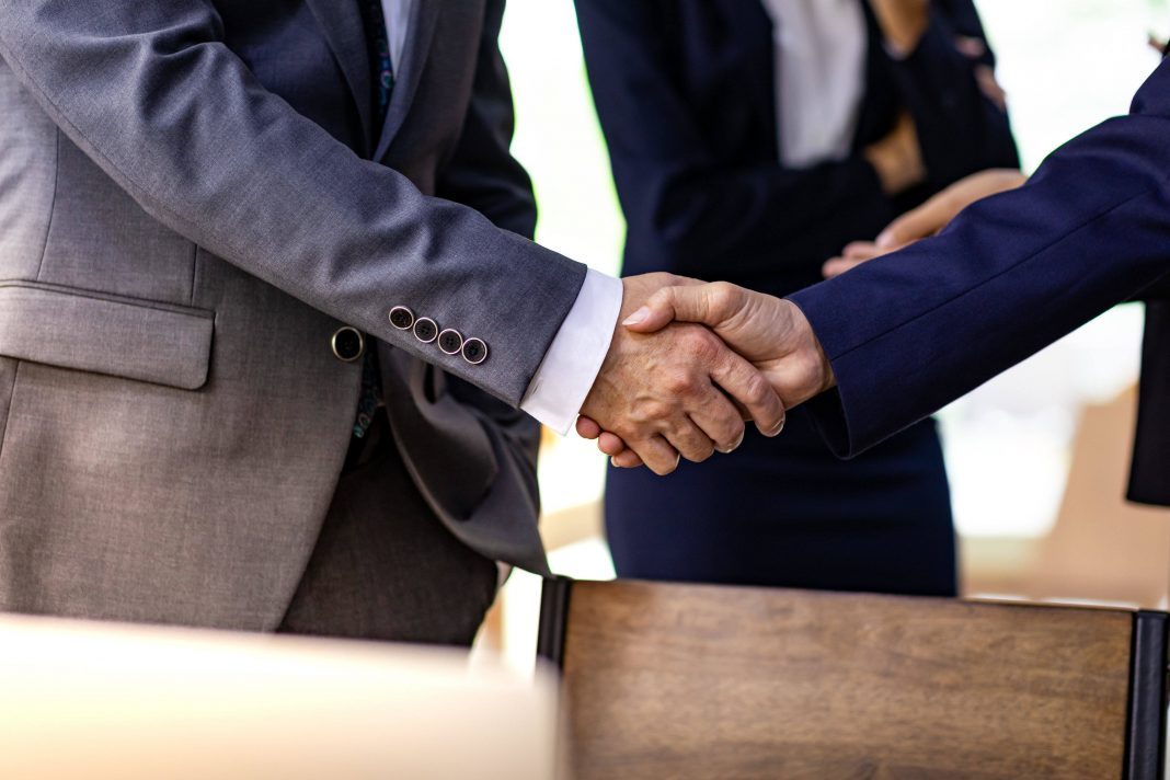 Two suited up businessman in the middle of a handshake