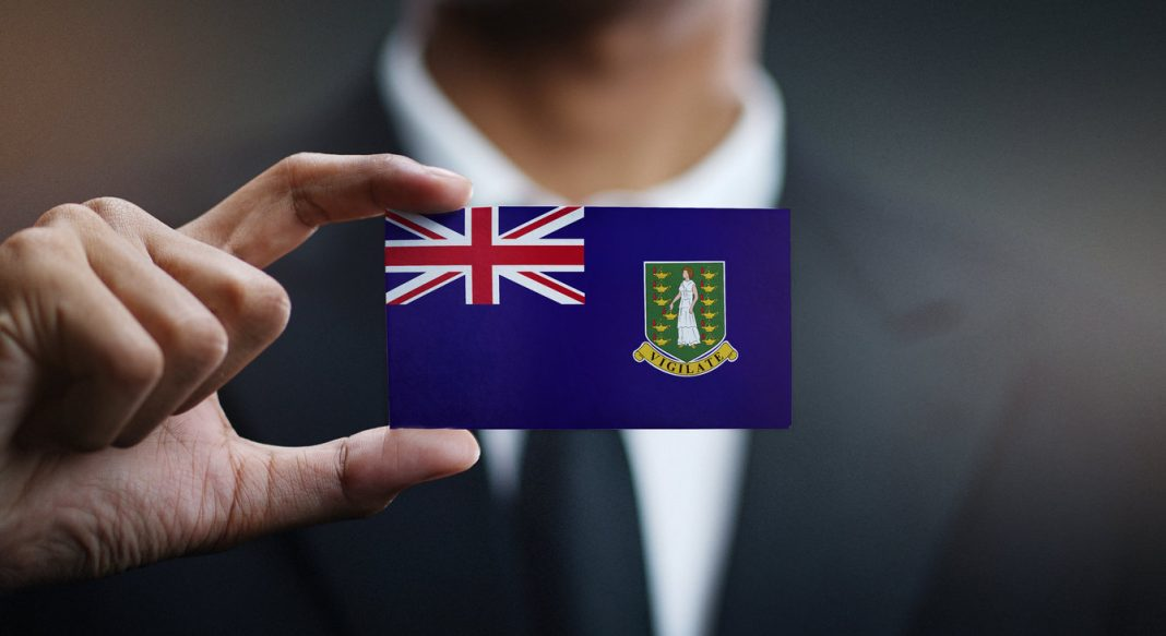 A businessman holding a card with the British Virgin Islands flag on it.