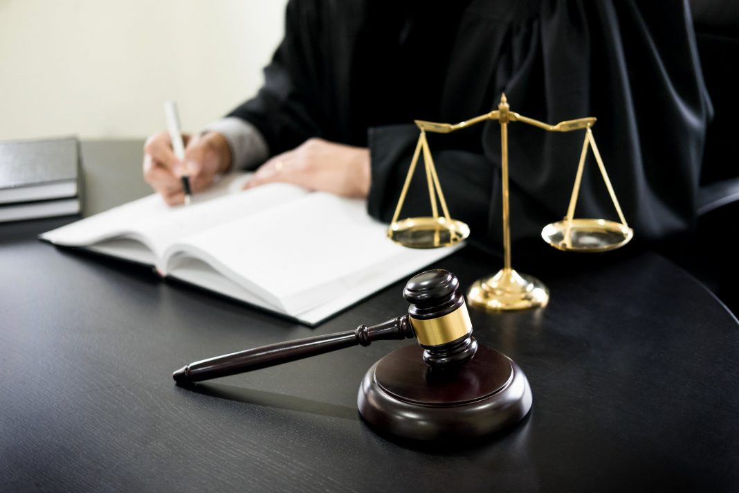 A judge sitting behind a wooden desk with a gavel and scales of justice on top of it