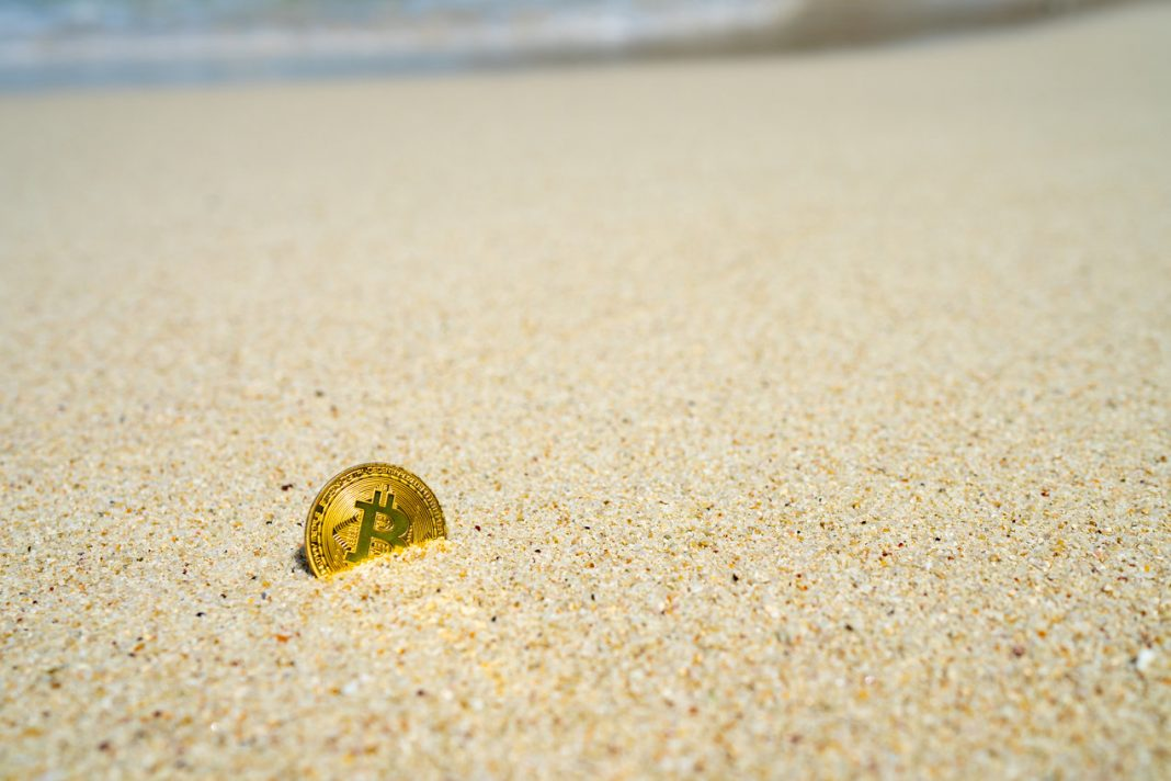 A tranquil beach where a golden coin with Bitcoin's logo is semi-buried
