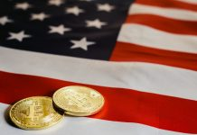 Physical coins with the bitcoin logo on them, left on top of a USA flag