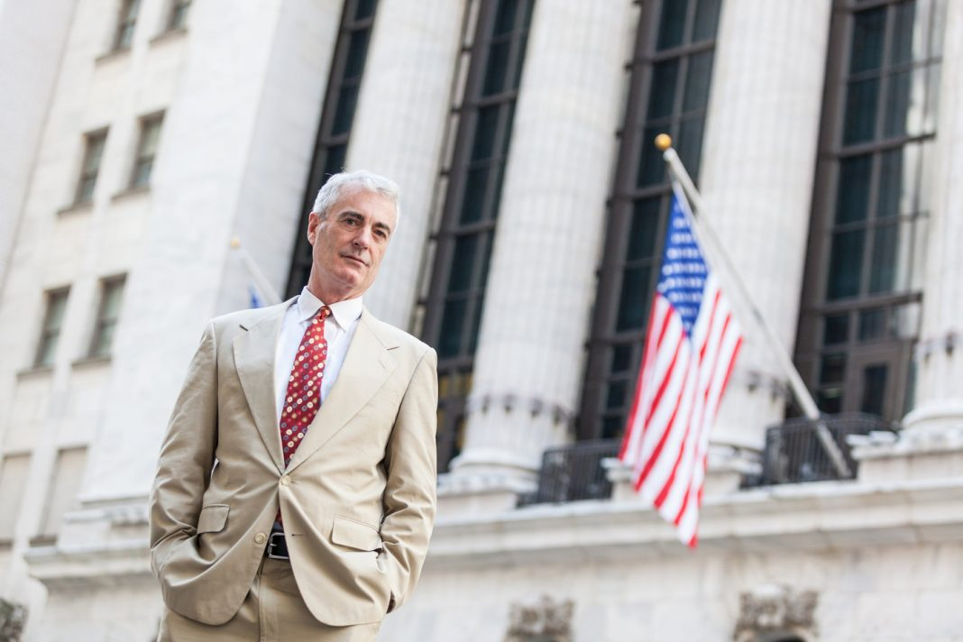 A senior businessman standing in New York next to an American flag