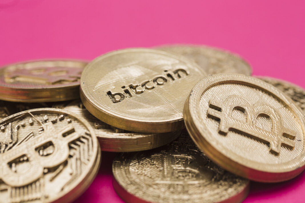 Bitcoin coins on a pink background