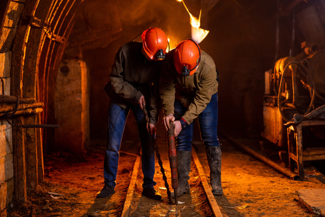Two young men in a working uniform and protective helmets, carrying out work in a mine