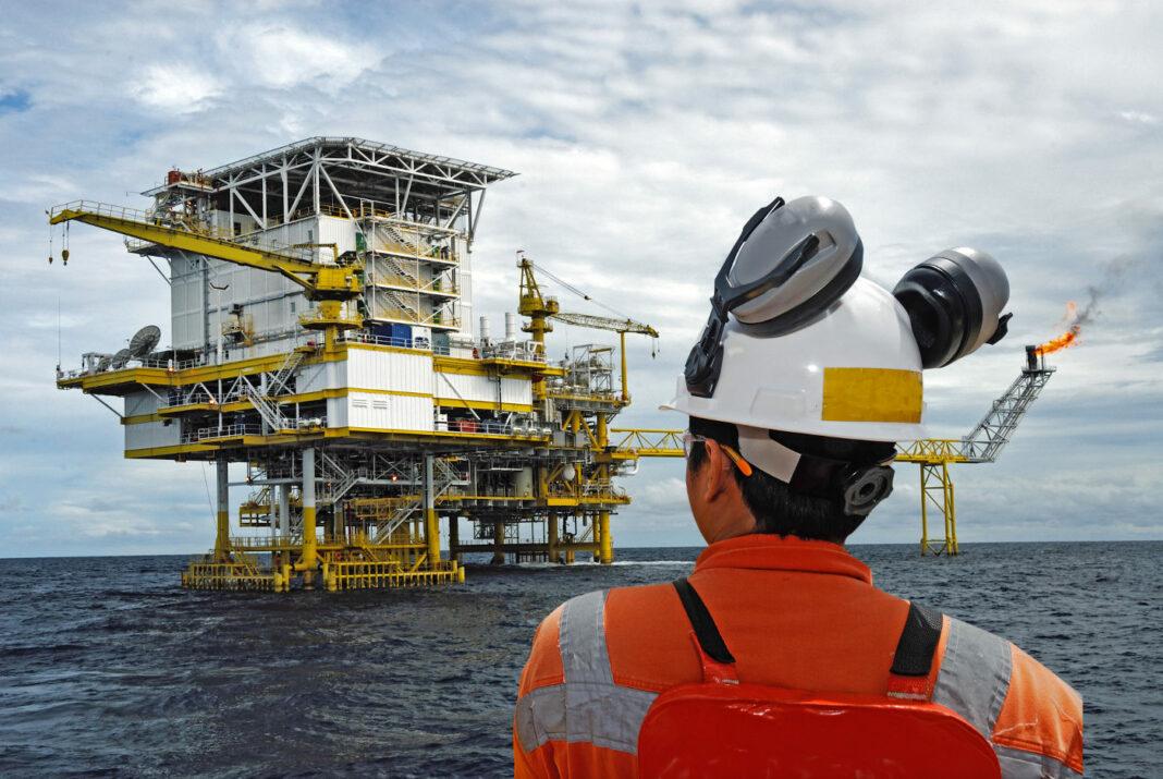 Oil worker looking at oil platform