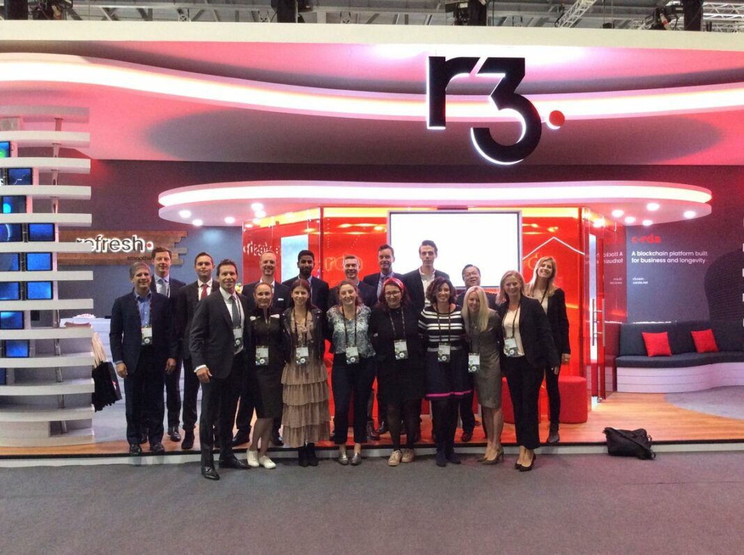 The R3 team in front of the R3 booth at the Sibos conference