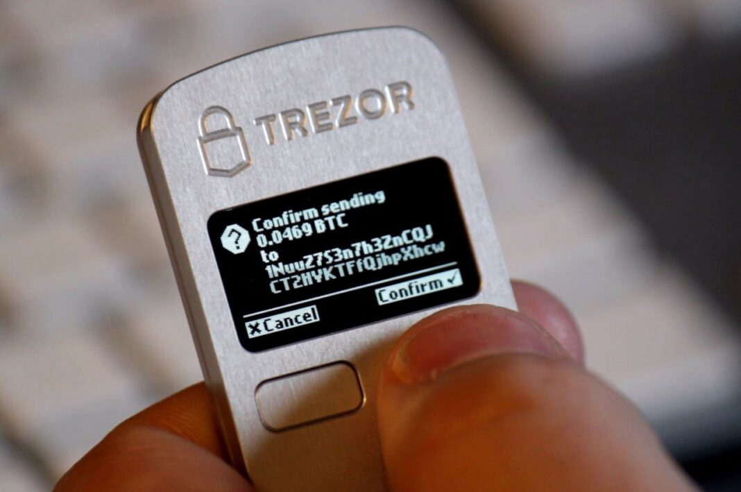Person using a Trezor One hardware wallet to confirm the sending of some bitcoin