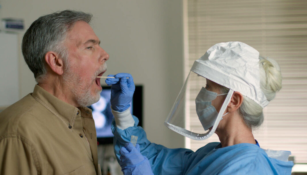 A mature Caucasian man in a clinical setting being swabbed by a healthcare worker