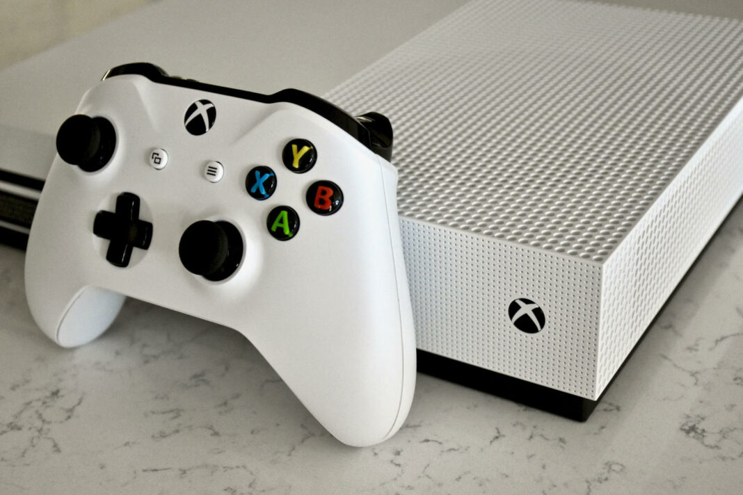 A White Xbox One S console and controller on a carrera marble surface