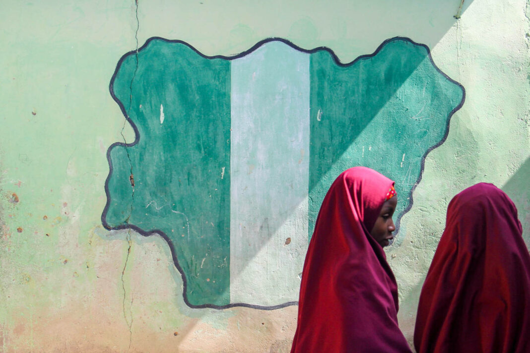 Girl students pass a classroom with the map and flag of Nigeria