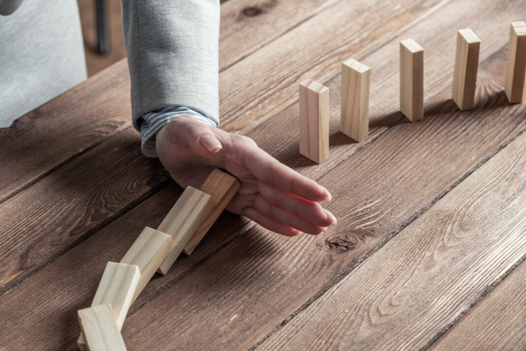 Businesswoman protecting dominoes from falling on wooden desk
