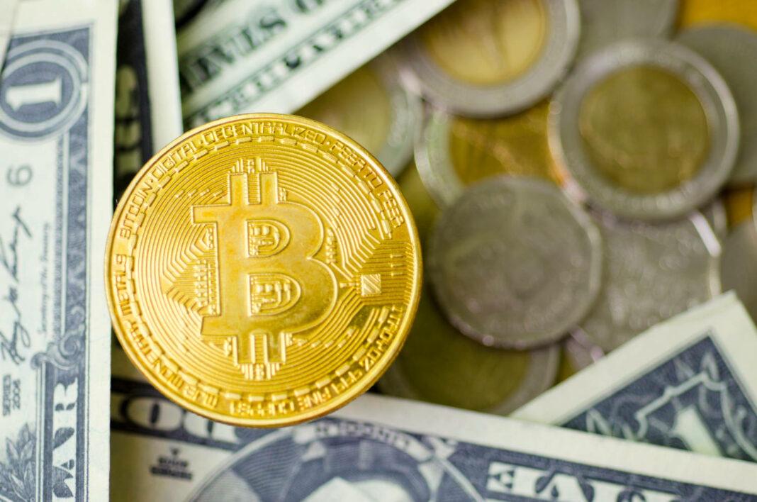 Bitcoin coin among dollar bills and coins