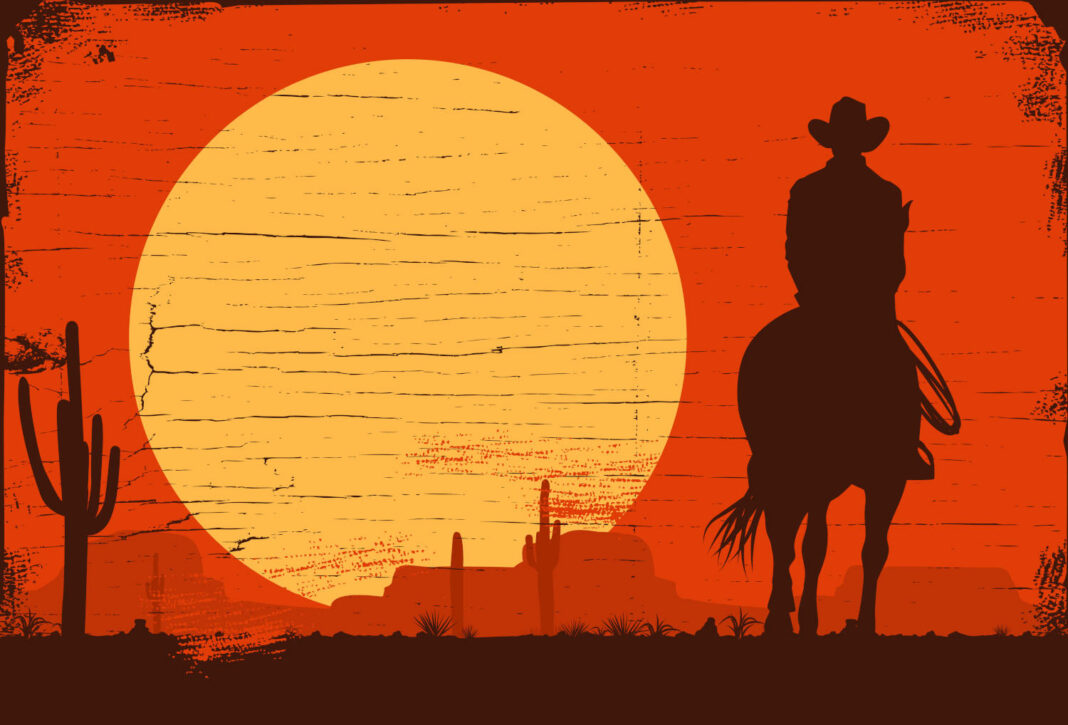 Cowboy riding in the desert at sunset