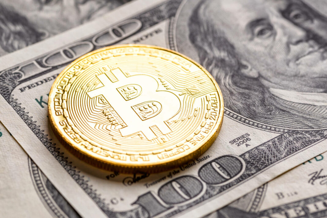 Bitcoin coin on top of a US dollar banknote