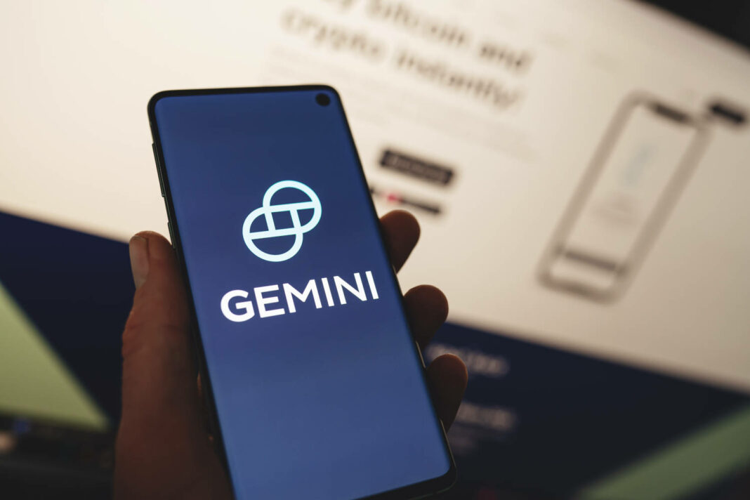 Man holding a smartphone with Gemini app