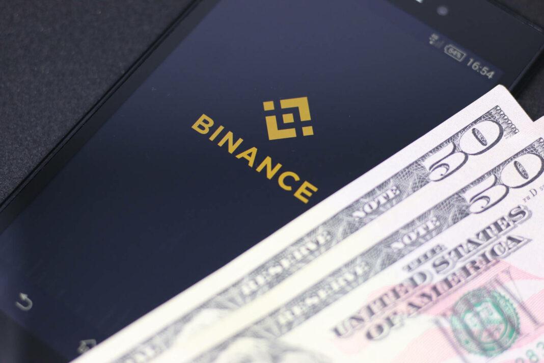 Binance android app on black background with few dollar bills