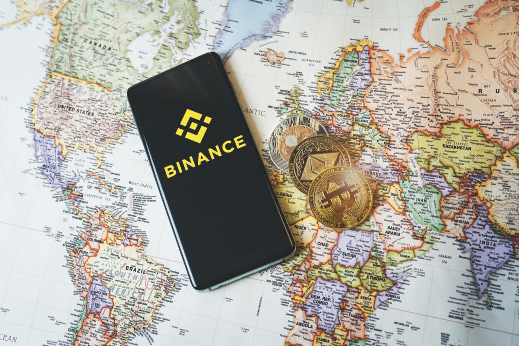 Binance app logo on a smartphone and crypto coins Bitcoin, Ethereum and XRP on a world map