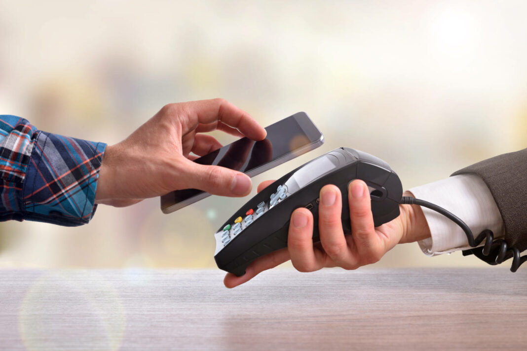 Customer paying a merchant with mobile phone with NFC technology