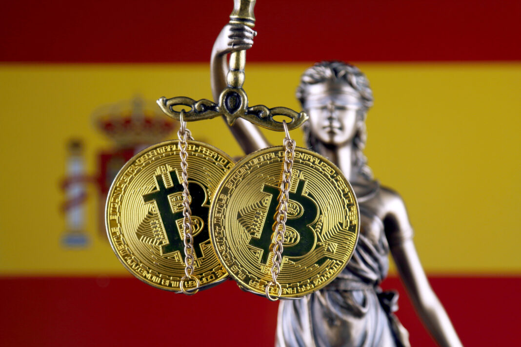 Symbol of law and justice, physical version of Bitcoin and Spain Flag